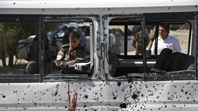 Afghan security personnel investigate a damaged minivan which was hit by a remote controlled bomb on the outskirts of Kabul, Afghanistan, Tuesday, July 15, 2014. Gul Agha Hashimi, the chief of criminal investigations with the Kabul police, said the explosion struck the minivan carrying seven staffers of the palace's media office on Tuesday morning. The blast killed two passengers and also wounded five people, including the driver. (AP Photo/Rahmat Gul)