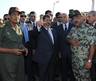 Egyptian Defence Minister Hussein Tantawi (L) and President Mohamed Morsi (C) visit a checkpoint in the northern Sinai on August 7. Morsi on Sunday ordered the surprise retirement of Tantawi and scrapped a constitutional document which handed sweeping powers to the military