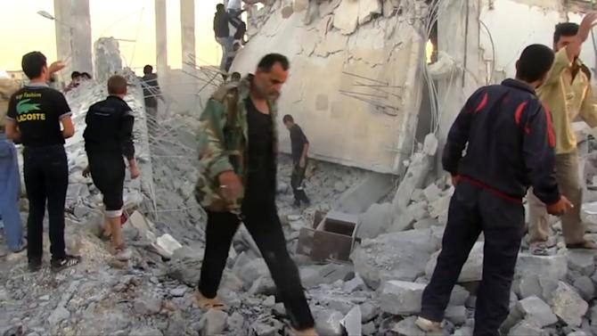 In this image taken from video obtained from Shaam News Network (SNN), which has been authenticated based on its contents and other AP reporting, Syrians dig through rubble of a building destroyed by a government airstrike as they search for survivors in Azaz, Syria, Friday, Sept. 28, 2012. A Syrian activist group, the Local Coordination Committees, said a Syrian warplane bombed the northern town of Azaz near the Turkish border, killing several people. (AP Photo/Shaam News Network SNN via AP video)