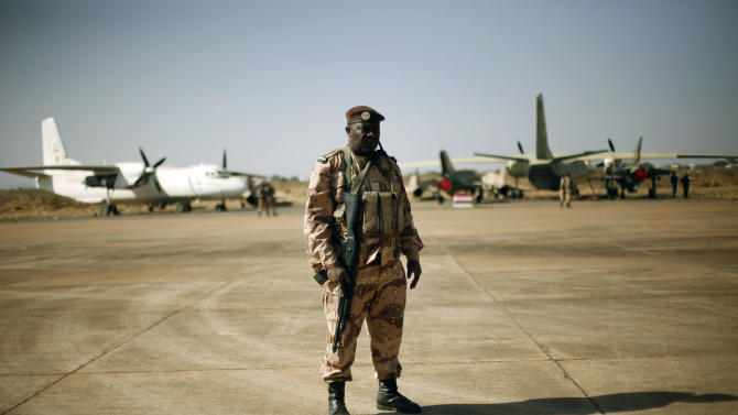 """A Mali National Guard soldier stands guard on the military side of  Bamako's airport Wednesday Jan. 16, 2013, during a joined visit to French and Malian troops by Mali's President  Dioncounda Traore and French Ambassador to Mali  Christian Rouyer. French troops pressed northward in Mali toward territory occupied by radical Islamists on Wednesday, military officials said, announcing the start of a land assault that will put soldiers in direct combat """"within hours."""" (AP Photo/Jerome Delay)"""