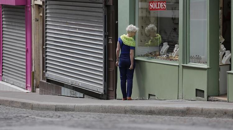 A woman makes her way past past opened and closed shops during a Sunday morning walk at the Butte Montmartre in Paris