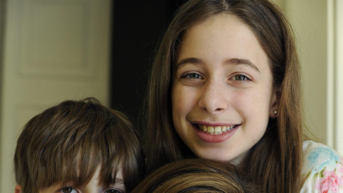 """In this March 12, 2012 photo, Bettina Siegel, center, poses with her son Asher, 9, and daughter Lily, 12, at their home in Houston. Siegel, whose blog """"The Lunch Tray"""" focuses on kids' food, was so upset over a report of ammonia-treated meat trimmings in school lunches she started an online petition asking Agriculture Secretary Tom Vilsack to """"put an immediate end to the use of 'pink slime' in our children's school food."""" As of Monday she had more than 175,000 online signatures. (AP Photo/Pat Sullivan)"""