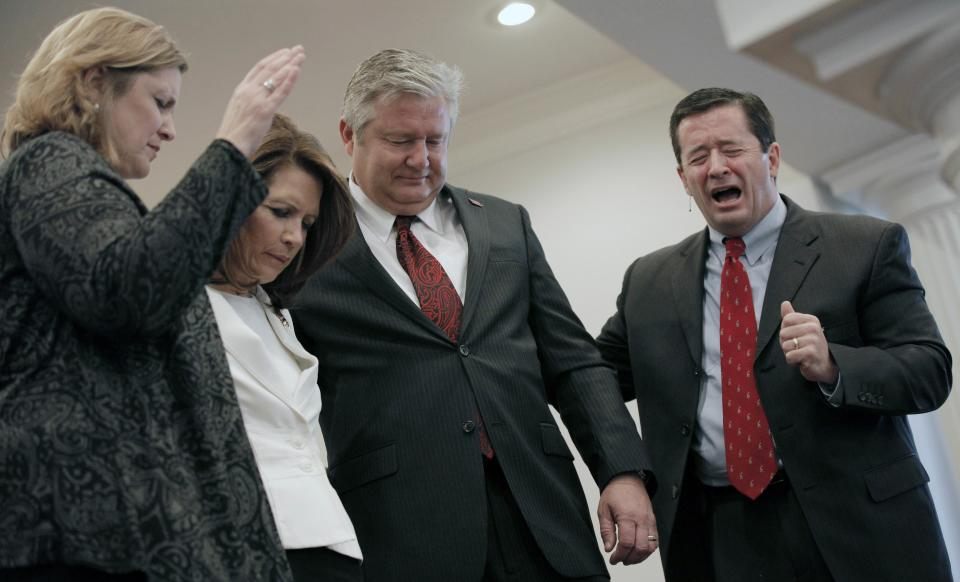 Republican presidential candidate, Rep. Michele Bachmann, R-Minn., and her husband Marcus are blessed by Pastor Bill Tvedt and his wife Julie during a campaign stop at Jubilee Family Church in Oskaloosa, Iowa, Sunday, Jan, 1, 2012. (AP Photo/Charlie Riedel)