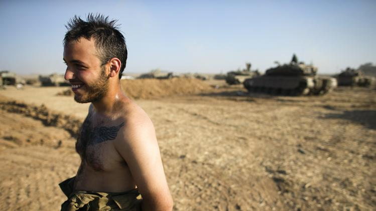 An Israeli soldier stands at a military staging area near the border with Gaza