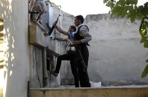 A Free Syrian Army fighter tries to climb a wall around…
