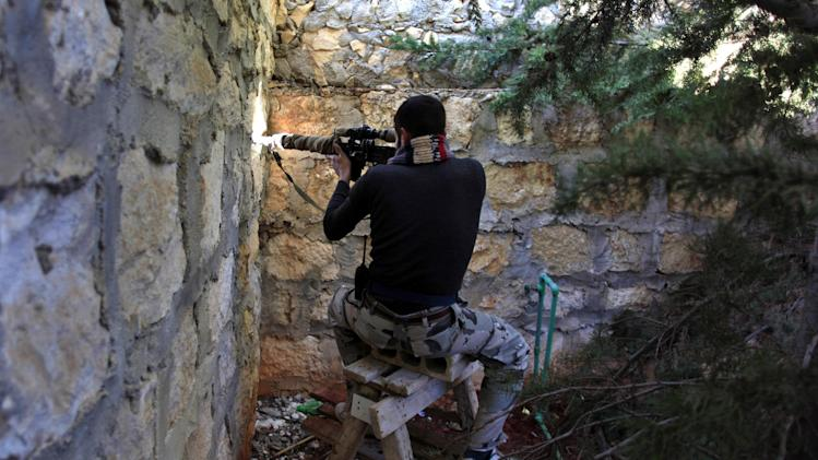 A Syrian rebel sniper aims at Syrian army position on the outskirts of Aleppo, Syria, Wednesday, Nov. 14, 2012. Heavy clashes between rebel units and Bashar Assad's troops were ongoing in the northern city of Aleppo, the Syrian Observatory for Human Rights said Wednesday. (AP Photo/Khalil Hamra)