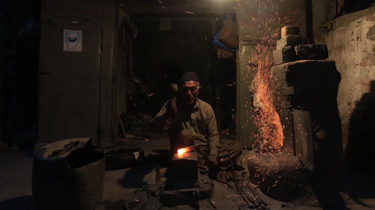 A man hammers on a hot iron to make a tool at his workshop in Rawalpindi