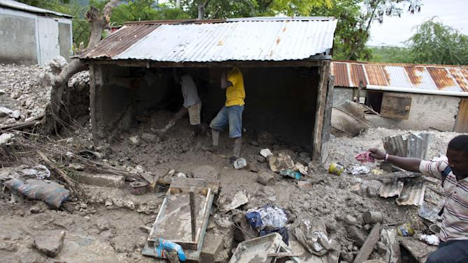 Residents salvage personal items after a mudslide triggered by Tropical Storm Erika left it partially submerged, in Montrouis, Haiti, Saturday, Aug. 29, 2015. Erika dissipated early Saturday, but it left devastation in its path on the small eastern Caribbean island of Dominica, and parts of Haiti, authorities said. (AP Photo/Dieu Nalio Chery)