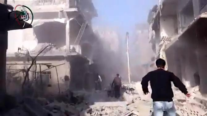 In this photo taken from video obtained from the Shaam News Network, which has been authenticated based on its contents and other AP reporting, Syrian men run to aid injured people in the aftermath of a strike by Syrian government warplanes on the residential neighborhood of Maadamiyeh south of Damascus, Syria, Monday, Jan. 14, 2013.  A Syrian airstrike slammed into a house in a rebellious suburb of Damascus early Monday, killing at least a dozen people including eight children, activists said, as President Bashar Assad's regime ramped up its operations against the opposition strongholds ringing the capital. (AP Photo/Shaam News Network via AP video)