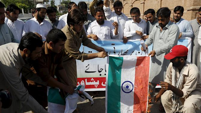 Supporters of Shabab-e-Milli, the youth wing of the Jamaat-e-Islami party burn a replica of the Indian flag during a protest in Peshawar