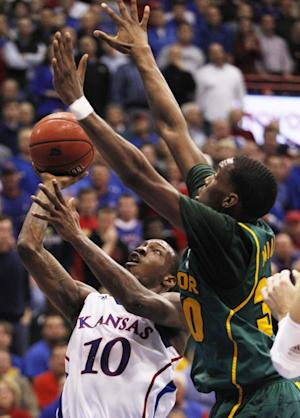Kansas guard Tyshawn Taylor (10) shoots while covered by Baylor forward Quincy Miller (30) during the first half of an NCAA college basketball game in Lawrence, Kan., Monday, Jan. 16, 2012. (AP Photo/Orlin Wagner)