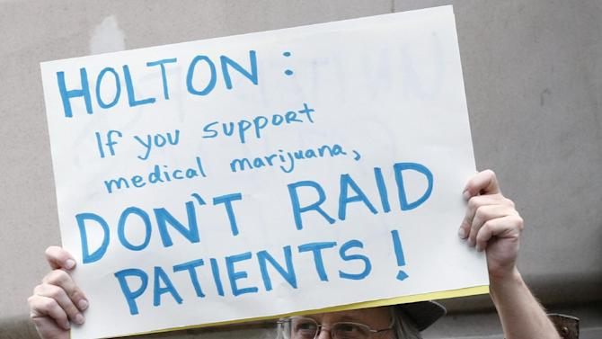 """File - In this April 27, 2012, file photo shows a protester outside the Portalnd City Club during the attorney general candidate's debate between Dwight Holton and Ellen Rosenblum, in Portland, Ore. Medical marijuana advocates have a message for Democratic leaders and federal prosecutors with an eye on political office: Don't mess with pot. Pushing back against the Obama administration's crackdown on state medical marijuana programs, one of the nation's largest pro-pot groups is claiming credit for the defeat of a former federal prosecutor in the Democratic primary for Oregon attorney general. As interim U.S. attorney, Dwight Holton called Oregon's medical marijuana law a """"train wreck"""" and oversaw efforts to crack down on pot shops and marijuana gardens that claim to be operating under the state law. (AP Photo/Rick Bowmer, File)"""