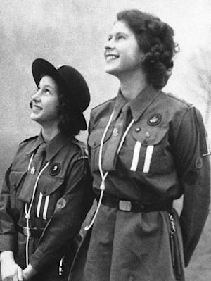 """FILE - This is a Feb. 20, 1943 file photo of Britain's Princess Elizabeth, right, and her sister, Princess Margaret as they  watch their carrier pigeon circle in the sky after they have released it with a message for Lady Baden-Powell.  It was one of the many messages sent by Girl Guides throughout Britain on Thinking Day which marks the Birthday late Lord Baden-Powell, founder of the Scout movement.  Britain's Girl Guides have dropped a reference to God in their pledge. Gone is the reference to loving God, replaced by a call to """"be true to myself and develop my beliefs."""" The new pledge unveiled Wednesday  June 19, 2013, does retain a reference to serving the queen. (AP Photo, File)"""
