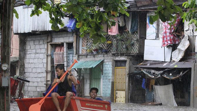 Residents make their way through a flooded area on a small boat during Tropical storm Fung-Wong in Pasay city, metro Manila