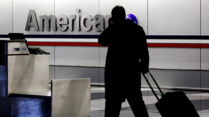 FILE - In this Tuesday, Nov. 29, 2011, file photo, a passenger walks through an American Airlines baggage claim area at O'Hare International Airport in Chicago. American Airlines said Thursday, May 16, 2013, that people carrying just a personal item that fits under the seat, not a rolling suitcases, will be allowed to board before most other passengers. American said that the change will speed up the boarding process and allow flights to take off sooner, helping the airline improve its on-time performance. (AP Photo/Nam Y. Huh, File)