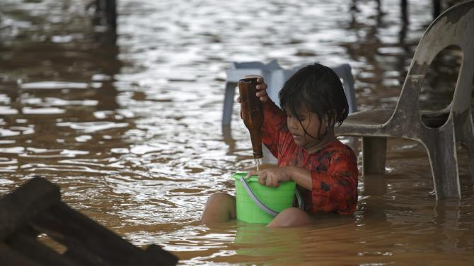A girl plays on a flooded street on the outskirts of Kota Bharu in Kelantan