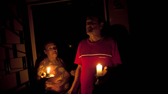 "In this April 8, 2013 photo, Pedro Martinez, 73, right, and his wife Aura, 60, hold lit candles during a power outage at their home in Valencia, Venezuela. ""This happens nearly every day,"" Martinez says of the blackout. It's was the day's second outage. The first struck just after noon. Outside Venezuela's capital, power outages, food shortages and unfinished projects abound; important factors heading into Sunday's election to replace Venezuela's late President Hugo Chavez, who died last month after a long battle with cancer. Polls show that support for acting President Nicolas Maduro, Chavez's hand-picked successor, may be eroding and constant power outages are a testament to the neglect many Venezuelans consider inexcusable in this major oil-producing state. (AP Photo/Ramon Espinosa)"