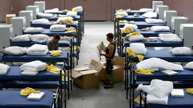 Workers arrange 200 beds and lockers in a sports hall of a school during preparations to receive asylum seekers, in Puchheim near Munich