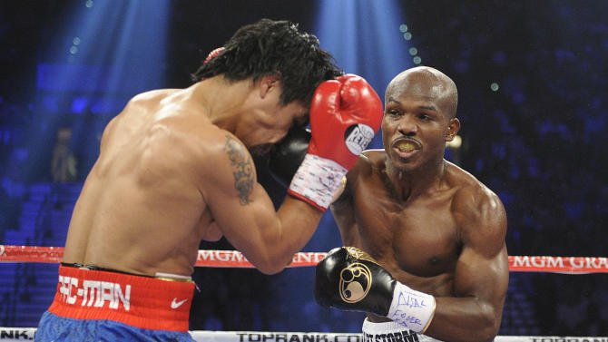 Manny Pacquiao, from the Philippines, left, covers up as Timothy Bradley, from Palm Springs, Calif., throws a punch in the first round of their WBO world welterweight title fight Saturday, June 9, 2012, in Las Vegas. (AP Photo/Chris Carlson)