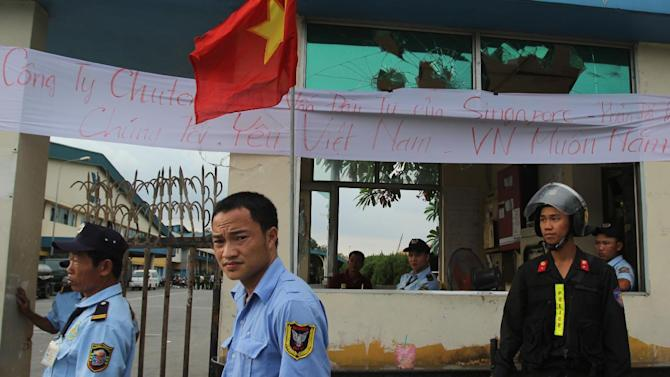 """Security staff guard the entrance to a Singaporean factory in an industrial park in Binh Duong province, Vietnam Saturday, May 17, 2014, after mobs attacked foreign owned factories following anti-China protests. Vietnam's prime minister ordered an end Saturday to all """"illegal protests"""" in the country after a week of violent demonstrations against China's deployment of an oil rig in a disputed section of the South China Sea. Banner reads: """"This is a Singaporean owned company. We love Vietnam"""". (AP Photo/Hau Dinh)"""