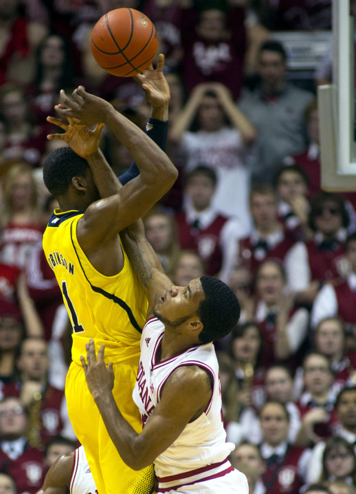 Michigan's Glenn Robinson III (1) is fouled by Indiana's Jeremy Hollowell (33) as he takes a shot during the second half of an NCAA college basketball game Saturday, Feb. 2, 2013, in Bloomington, Ind.