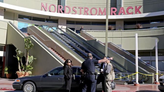 Los Angeles police investigators stand outside a Nordstrom Rack store at Howard Hughes Center near Los Angeles International Airport Friday, Jan. 11, 2013. Robbers stabbed a clothing store employee and sexually assaulted another during an hours-long hostage drama that ended early Friday with a police SWAT team surging into the shop and rescuing 14 workers. No robbers had been found by mid-morning. The ordeal began at about 11 p.m. when a man called 911 and reported that his girlfriend had called and said there were gunmen in the store, Lt. Andy Neiman said. (AP Photo/Reed Saxon)