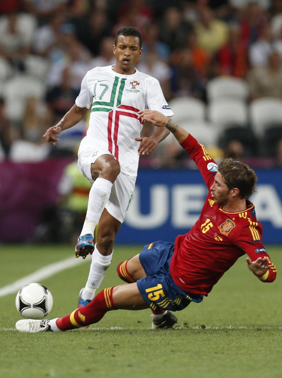 Portugal's Nani is tackled by Spain's Sergio Ramos during the Euro 2012 soccer championship semifinal match between Spain and Portugal in Donetsk, Ukraine, Wednesday, June 27, 2012. (AP Photo/Jon Super)