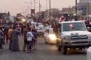 In this still image posted on a militant Twitter account on Wednesday, June 11, 2014, which has been authenticated based on its contents and other AP reporting, militants parade down a main road in Mosul, Iraq. Iraqi officials say al-Qaida-inspired militants who this week seized much of the country's Sunni heartland have pushed into an ethnically mixed province northeast of Baghdad, capturing two towns there.(AP Photo/militant source via Twitter)