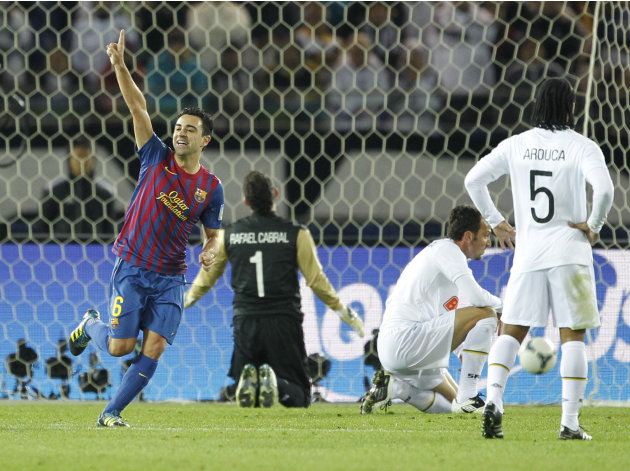 Spain's FC Barcelona midfielder Xavi Hernandez, left, celebrates his goal as Brazil's Santos FC goalkeeper Rafael Cabral (1) and defender Carles Puyolin (5) react in the first half of their final matc