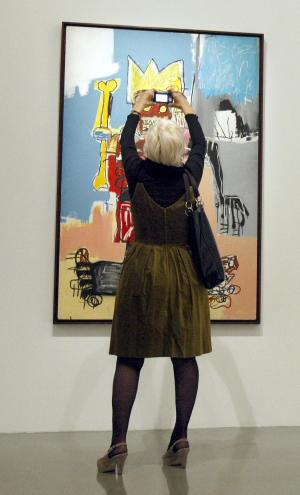 "A member of the media takes a snapshot of ""Dustheads"", a 1982 painting by American artist Jean-Michel Basquiat which is part of an exhibition of 150 works of art by Basquiat, shown from Oct. 15, 2010 to Jan. 30, 2011 at the Museum of Modern Art in Paris, Thursday Oct. 14, 2010.(AP Photo/Remy de la Mauviniere)"