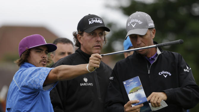 Rickie Fowler of the United States, left, and Phil Mickelson of the United States, center, gesture during a practice round at Royal Lytham & St Annes golf club ahead of the British Open Golf Championship, Lytham St Annes, England Tuesday, July  17, 2012. Man at right is unidentified. (AP Photo/Tim Hales)