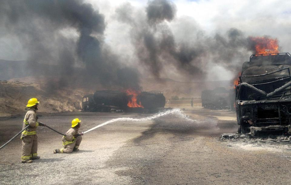 Afghan firefighter men spray water on a burning NATO supply truck in Samangan, north of Kabul, Afghanistan, Wednesday, July 18, 2012. Afghan officials say a magnetic bomb placed on a truck exploded and destroyed 22 NATO supply vehicles in northern Afghanistan. (AP Photo/Javed Dehsabzi)