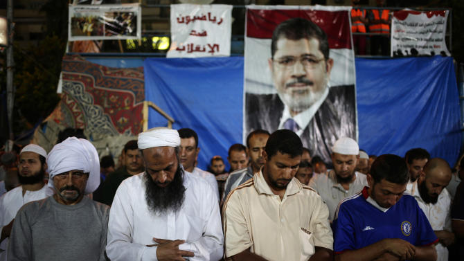 "Supporters of Egypt's ousted President Mohammed Morsi pray outside Rabaah al-Adawiya mosque, where supporters of Egypt's ousted President Mohammed Morsi have installed a camp and hold daily rallies at Nasr City, in Cairo, Egypt, late Tuesday, July 30, 2013. Egypt's military gave the ousted president his first contact with the outside world since removing him from office, allowing Europe's top diplomat Tuesday to meet with Mohammed Morsi in his secret detention. She emerged from her two-hour talks with him urging all sides to move on toward a peaceful transition. Arabic on the banner in the center reads: ""Athletes against the coup."" (AP Photo/Hassan Ammar)"