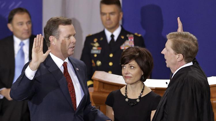 FILE - This Jan. 7, 2013, file photo shows Utah Attorney General John Swallow, left, being sworn in by Chief Justice Matthew B. Durrant, right, while his wife Suzanne Seader watches at the Utah Sate Capitol Rotunda, in Salt Lake City. Swallow, who was sworn into office last Monday, strongly denies the allegations and maintains he only offered to connect Johnson with a lobbying firm. Swallow, a Republican, said he told Johnson he would not interfere with the FTC investigation or advocate for Johnson to the U.S. attorney. (AP Photo/Rick Bowmer)