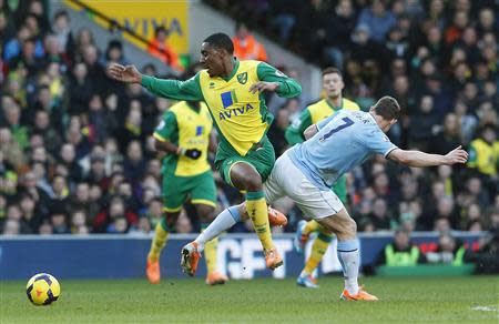 Manchester City's Milner challenges Norwich City's Fer during their English Premier League soccer match at Carrow Road in Norwich, eastern England