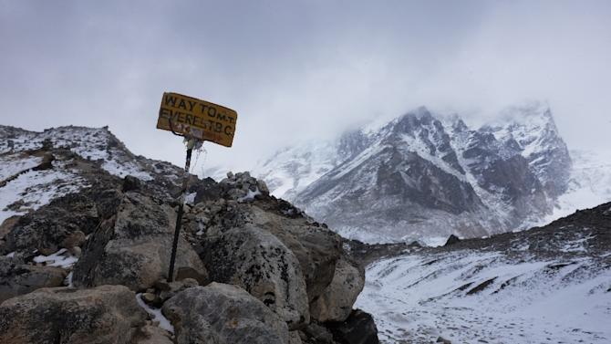A sign showing the way to Everest Base Camp high in the Khumb Glacier stands among rocks on April 26, 2015