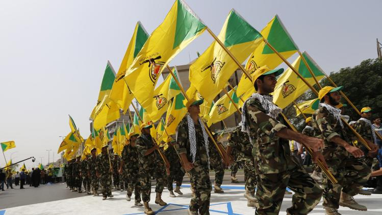 Iraqi Shi'ite Muslim men from the Iranian-backed group Kataib Hezbollah wave the party's flags during a parade marking the annual Quds Day in Baghdad