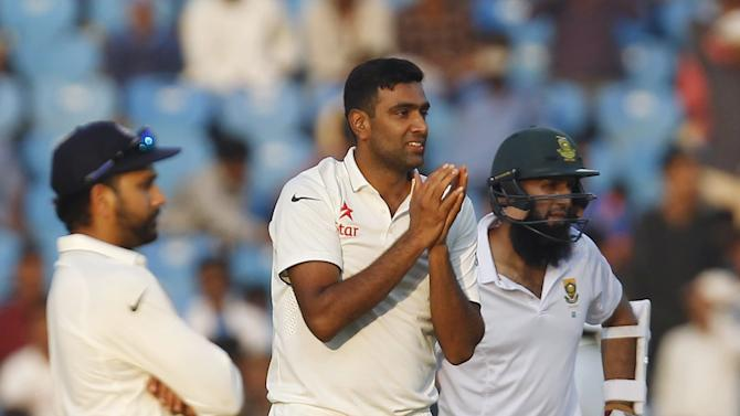 India's Ashwin reacts as his team mate Sharma and South Africa's captain Amla look on during the second day of their third test cricket match in Nagpur