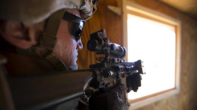 A U.S. Marine from Fox Company, 2nd Battalion 1st Marines, 13th Marine Expeditionary Unit aims his weapon through a window during a non-live fire MOUT training at US Marine Corps: Marines Air Ground Combat Center in Twentynine Palms