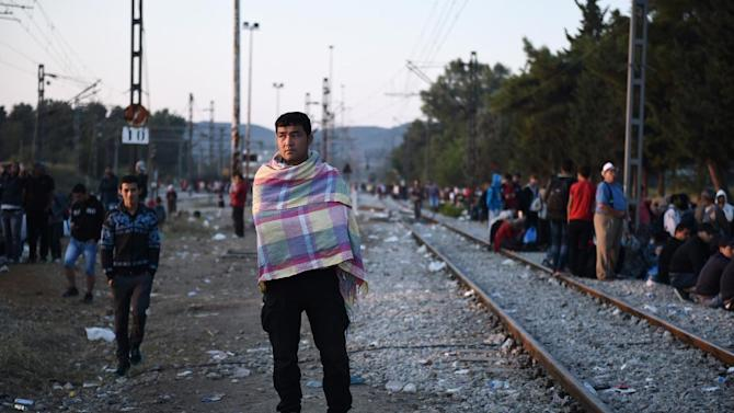 Refugees wait among railway tracks at the border town of Idomeni, northern Greece, to be allowed by Macedonian police to cross the border from Greece to Macedonia, Sunday, Aug. 30, 2015. The United Nations' refugee agency announced Friday that 200,000 refugees, the vast majority from Syria and Afghanistan, have entered Greece in 2015, more than four times the entire 2014 figure. (AP Photo/Giannis Papanikos)