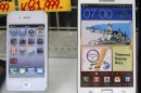 File photo shows an Apple iPhone and a Samsung Galaxy Note displayed at a shop in Tokyo