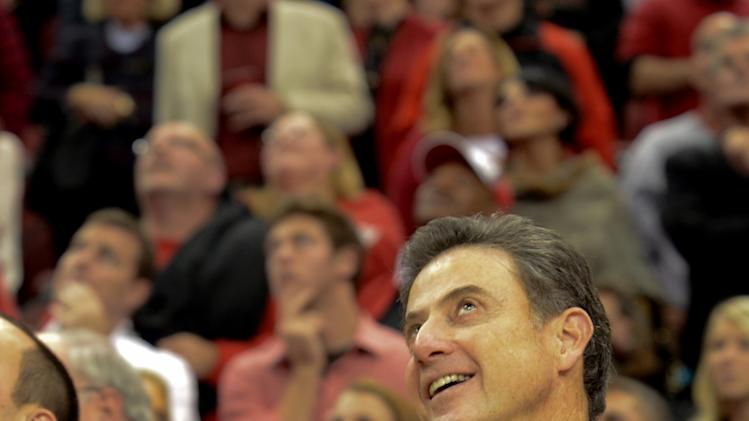 Louisville's coach Rick Pitino, right, and his wife Joanne Pitino, left, watch a video of coach Pitino's career after winning his 600 career NCAA college basketball game against Tennessee-Martin, Friday, Nov. 11, 2011, in Louisville, Ky. Louisville won 83-48. (AP Photo/ Daniel R. Patmore)