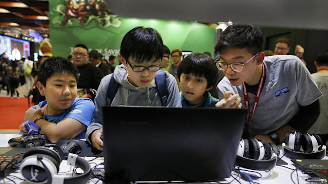 A group of boys tries out a new video game at the Taipei Game Show in Taipei, Taiwan, Wednesday, Jan. 28, 2015. The game show, one of the leading digital interactive gaming events in Asia, will run from Jan. 28 through Feb. 1. (AP Photo/Wally Santana)