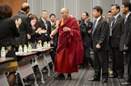 Tibet&#39;s spiritual leader Dalai Lama (C) is welcomed by Japanese parliament members at the upper house members&#39; office building in Tokyo on November 13, 2012. The Dalai Lama urged Japanese lawmakers Tuesday to visit Tibet to find out the reasons for a spate of self-immolations