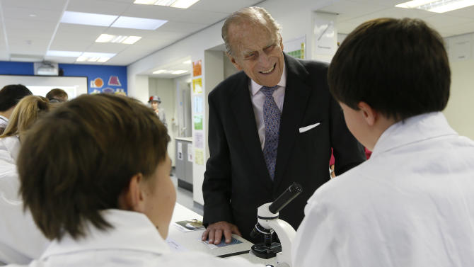 Britain's Prince Philip,  Duke of Edinburgh meets pupils in a science lesson during a visit to Holyport College near Maidenhead, Berkshire in England, Friday, Nov. 28, 2014. Holyport College is an all-ability, co-educational day and boarding school for students aged 11 to 19 years and is a state-funded 'free school,' which opened in Sept. 2014. (AP Photo/Kirsty Wigglesworth, Pool)