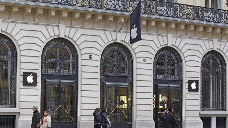 Parisians and tourists wander in front of the Apple store located near the Paris Opera, Tuesday, Jan. 1, 2013. A robbery took place at the flagship store on Monday, a few hours after the close of business. (AP Photo/Remy de la Mauviniere)