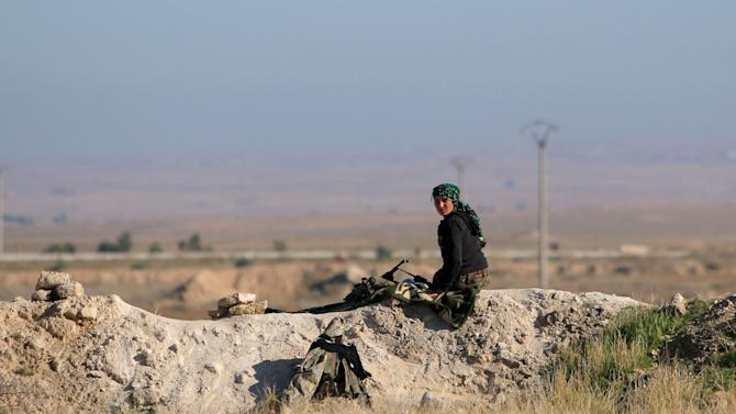 A fighter from the Democratic Forces of Syria sits at a guard post in the 121 Regiment base, after the group took control of it from Islamic State militants, in the town of al-Melabiyyah