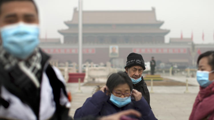 Tourists put on their masks after they posed for souvenir photos as they visit Tiananmen Square on a severely polluted day in Beijing, China, Tuesday, Feb. 25, 2014. Pollution across a large swath of northern China worsened on Tuesday. (AP Photo/Alexander F. Yuan)