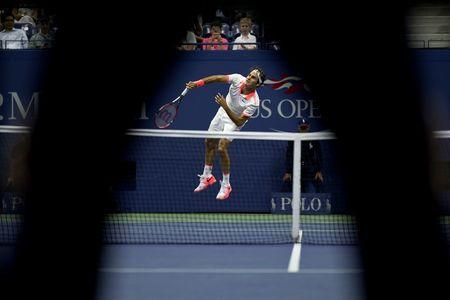 Federer of Switzerland is seen past the legs of an umpire as he serves to Darcis of Belgium during their second round match at the U.S. Open Championships tennis tournament in New York