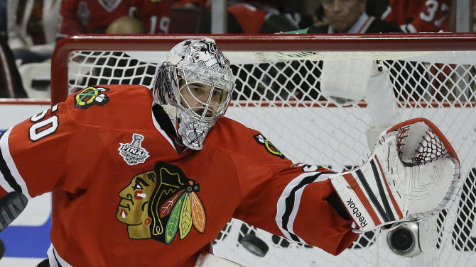 Chicago Blackhawks goalie Corey Crawford (50) reaches to glove a shot by the Boston Bruins in the first period during Game 5 of the NHL hockey Stanley Cup Finals, Saturday, June 22, 2013, in Chicago. (AP Photo/Nam Y. Huh)
